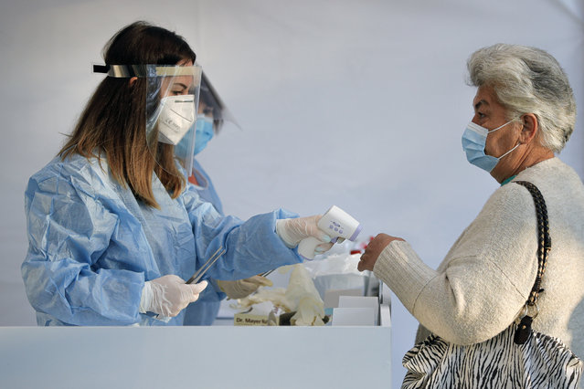An electoral staff member checks the temperature of a woman, wearing a face mask for protection against the COVID-19 infection, before allowing her in a voting station in Bucharest, Romania, Sunday, September 27, 2020. Some 19 million registered voters are choosing local officials, council presidents and mayors to fill more than 43,000 positions across the European Union nation. (Photo by Vadim Ghirda/AP Photo)