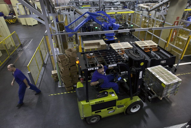 Workers lift boxes of R$ 0.25, or 25 centavos, at the end of the production line at the Casa da Moeda, the national mint, in the Santa Cruz suburb of Rio de Janeiro, Brazil, on Tuesday, March 5, 2013. Brazil is likely to keep its key interest rate at a record low for the third straight meeting, as policy makers are caught between a fragile economic recovery and faster-than-expected inflation. (Photo by Dado Galdieri/Bloomberg)