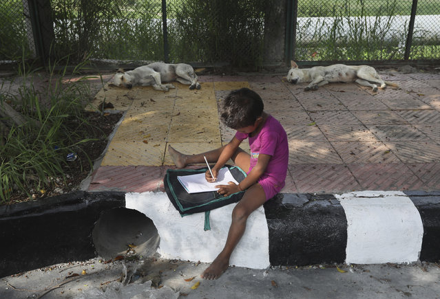 A child practices writing during a sidewalk class taught by an Indian couple, Veena Gupta and her husband Virendra Gupta, in New Delhi, India, on September 3, 2020. It all began when Veena's maid complained that with schools shut, children in her impoverished community were running amok and wasting time. The street-side classes have grown as dozens of children showed keen interest. Now the Guptas, with help from their driver, teach three different groups three times a week, morning and evening. While many private schools switched to digital learning and online classes, children in most government-run schools either don't have that option or don't have the means to purchase digital learning tools like laptops and smartphones. (Photo by Manish Swarup/AP Photo)