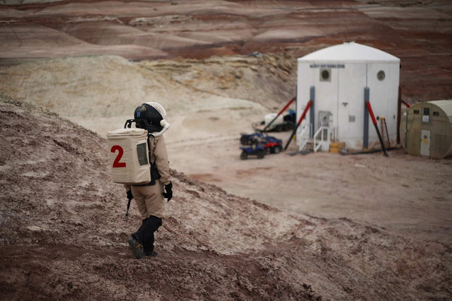 Csilla Orgel, a geologist of Crew 125 EuroMoonMars B mission, makes her way back to the Mars Desert Research Station (MDRS) in the Utah desert March 3, 2013. The MDRS aims to investigate the feasibility of a human exploration of Mars and uses the Utah desert's Mars-like terrain to simulate working conditions on the red planet. Scientists, students and enthusiasts work together developing field tactics and studying the terrain. All outdoor exploration is done wearing simulated spacesuits and carrying air supply packs and crews live together in a small communication base with limited amounts of electricity, food, oxygen and water. Everything needed to survive must be produced, fixed and replaced on site. (Photo by Jim Urquhart/Reuters)