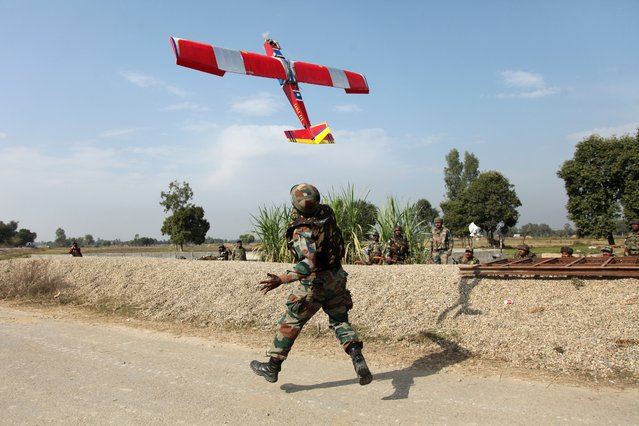 An Indian army soldier runs after a drone being sent for surveillance during a gunbattle with armed suspected militants at Pindi Khattar village in Arnia border sector, about 43 kilometers (27 miles) south of Jammu, India, Friday, November 28, 2014. Heavily armed suspected militants fought a fierce gunbattle with soldiers in the Indian portion of Kashmir that started Thursday, and three civilians were among the nine dead, authorities said. (Photo by Channi Anand/AP Photo)