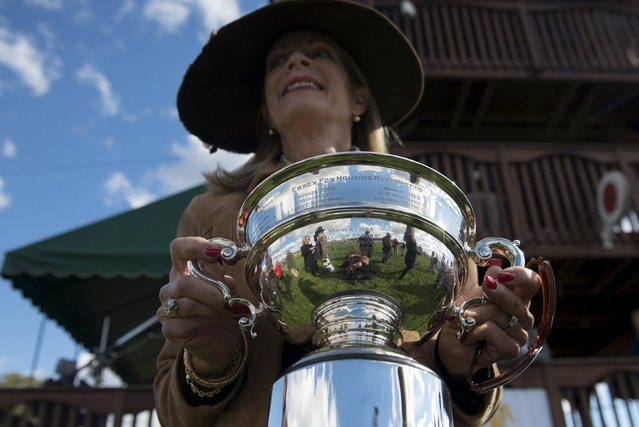 An official from the Far Hills Race Day committee holds a trophy for the winner of a race at the Far Hills Race Day at Moorland Farms in Far Hills, New Jersey, October 17, 2015. (Photo by Stephanie Keith/Reuters)