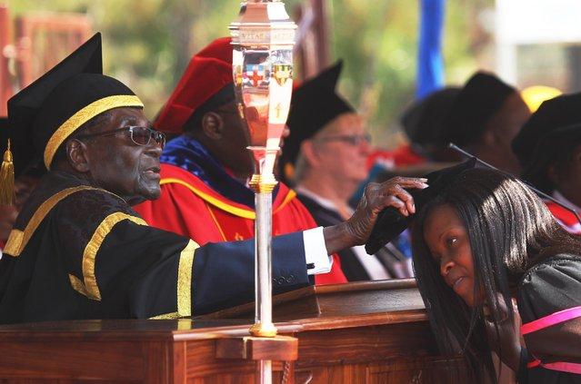 Zimbabwean President Robert Mugabe, left, places a cap on a student at the University of Zimbabwe, during graduation ceremony in Harare, Thursday, September 29, 2016. (Photo by Tsvangirayi Mukwazhi/AP Photo)