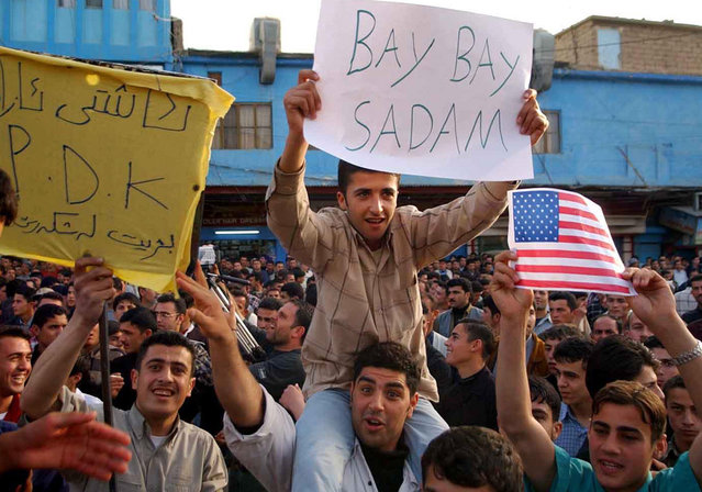 "Iraqi Kurds wave banners and U.S. and British flags in the northern Iraqi town of Dohuk, on April 9, 2003, to celebrate the arrival of U.S. led coalition forces' in Baghdad. Iraqi Kurds shouted for joy and fired in the air on Wednesday after U.S. forces entered Baghdad. ""It's all over in Baghdad"", said 29-year-old Rafiq Baway, who heard the news on satellite TV in the city of Sulaimaniya. He believed it would lead to the fall of Kirkuk, the northern oil hub where Kurds accuse Saddam of expelling Kurdish inhabitants and replacing them with Arabs. (Photo by Reuters/The Atlantic)"