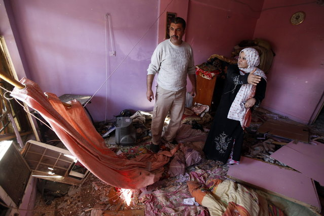 Iraqis examine damage inflicted on their house by a car bomb attack in AL-Mashtal district in Baghdad March 19, 2013. Car bombs and a suicide blast hit Shi'ite districts of Baghdad and south of Iraq's capital on Tuesday, killing at least 50 people on the 10th anniversary of the invasion that ousted Saddam Hussein. (Photo by Mohammed Ameen/Reuters)