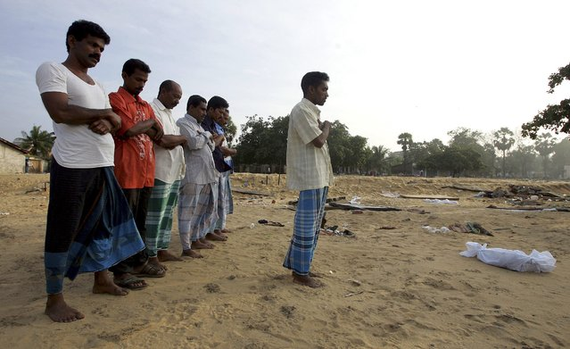 Sri Lankan Muslims pray for an infant killed in a tsunami, prior to the infant's burial in the town of Kalmunai on Sri Lanka's east coast in this January 14, 2005 file photo. (Photo by Arko Datta/Reuters)