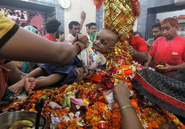 A Hindu man holds his baby seeking blessings for him at the Alopi Devi temple on the first day of the nine-day long Navratri festival in Allahabad, October 1, 2016. (Photo by Jitendra Prakash/Reuters)