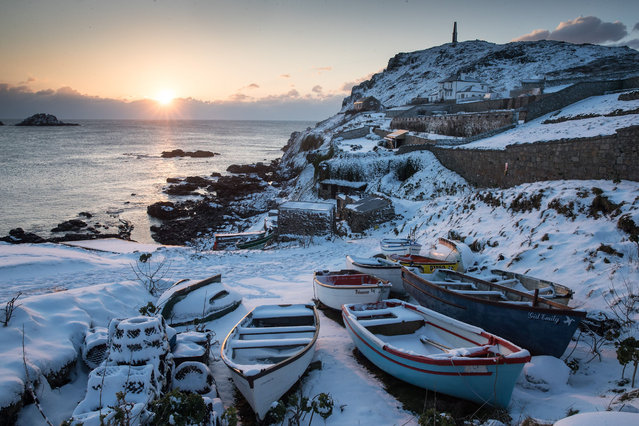 "The sun sets as snow covers fishing boats left at Priest's Cove at Cape Cornwall near Penzance on February 28, 2018 in Cornwall, England. Freezing weather conditions dubbed the ""Beast from the East"" has brought snow and sub-zero temperatures to many parts of the UK. Amber warnings are in place in northern England, the East Midlands, London, the d south-east of England. Scotland's weather warning has been upgraded to red, which meansby. (Photo by Matt Cardy/Getty Images)"