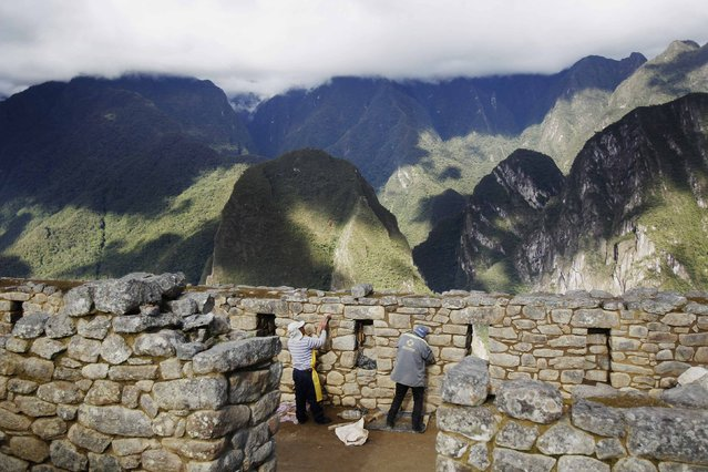 Workers take part in restoration tasks at the Inca citadel of Machu Picchu in Cusco December 2, 2014. (Photo by Enrique Castro-Mendivil/Reuters)