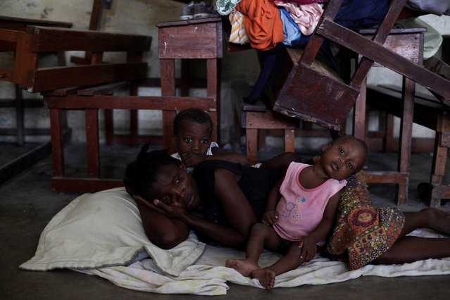 A woman with two of her children rest on the floor at the shelter set up in the Lycee Philippe Guerrier ahead of Hurricane Matthew in Les Cayes, Haiti, October 3, 2016. (Photo by Andres Martinez Casares/Reuters)