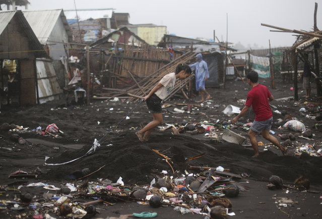 Residents begin cleaning their homes after strong waves from Typhoon Hagupit battered a coastal village in Legazpi, Albay province, eastern Philippines on Monday, December 8, 2014. (Photo by Aaron Favila/AP Photo)