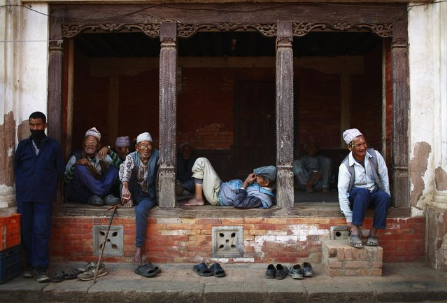 Men pass their time sitting along a street in Bhaktapur, Nepal, on April 4, 2013. (Photo by Navesh Chitrakar/Reuters)