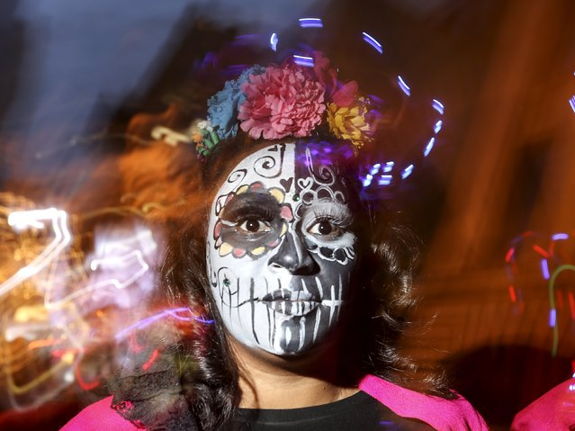 "A reveler dressed in a ""Dia de Muertos"" or ""Day of the Dead"" theme poses for a photo while they take part in the Greenwich Village Halloween Parade in the Manhattan borough of New York, October 31, 2015. (Photo by Carlo Allegri/Reuters)"