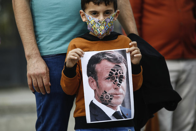 A child holds a photograph of France's President Emmanuel Macron, stamped with a shoe mark, during a protest against France in Istanbul, Sunday, October 25, 2020. Turkish President Recep Tayyip Erdogan on Sunday challenged the United States to impose sanctions against his country while also launching a second attack on French President Emmanuel Macron. Speaking a day after he suggested Macron needed mental health treatment because of his attitude to Islam and Muslims, which prompted France to recall its ambassador to Ankara, Erdogan took aim at foreign critics. (Photo by Emrah Gurel/AP Photo)