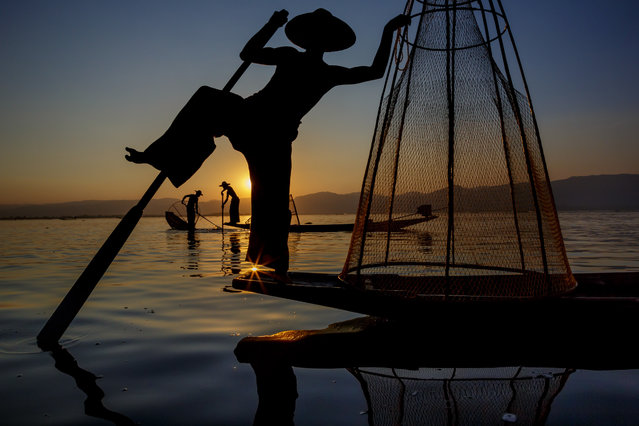 "Fishermen on Inle Lake, Myanmar. ""Here people practice a very unique style of fishing, gently lowering thimble-shaped nets in a very shallow lake over fish hiding in the water grasses; they then rap their oar against the net, disturbing the fish and causing them to swim into the net"". (Photo by Art Wolfe/The Guardian)"