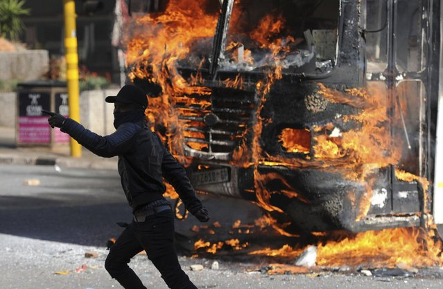 A protesting student runs past a burning bus off campus outside the University of the Witwatersrand in Johannesburg, South Africa on Monday, October 10, 2016. Tear gas and water cannon were fired as hundreds of students protested at the university amid a bitter national dispute with university managers and the government over demonstrators' demands for free education, forcing student into the neighbouring city streets. (Photo by AP Photo)