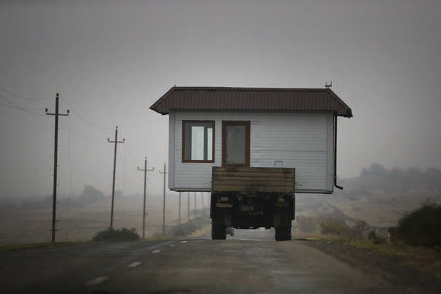 A family drives a truck loaded with a small house along a highway as they leave their home village in the separatist region of Nagorno-Karabakh, Wednesday, November 18, 2020. (Photo by Sergei Grits/AP Photo)