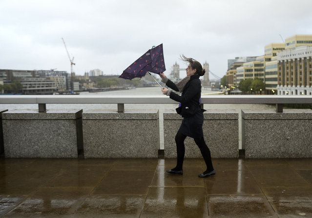 A commuter loses control of her umbrella as she braves the wind and rain while crossing London Bridge in London October 28, 2013. (Photo by Dylan Martinez/Reuters)