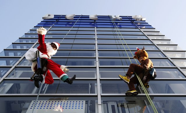 Window cleaners dressed as Santa Claus and a reindeer wave during an event to celebrate Christmas at a shopping mall in Tokyo December 24, 2014. (Photo by Yuya Shino/Reuters)