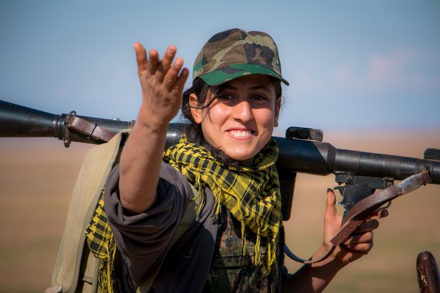 A Kurdish female fighter from the People's Protection Units (YPG) gestures as she carries her weapon near al-Hawl area where fighting between Islamic State fighters and fighters from Democratic Forces of Syria are taking place in south-eastern city of Hasaka, Syria November 10, 2015. (Photo by Rodi Said/Reuters)