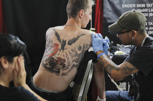 A man gets a tattoo during the International Tattoo Convention Bucharest 2016 in Bucharest, Romania, Sunday, October 16, 2016. (Photo by Vadim Ghirda/AP Photo)