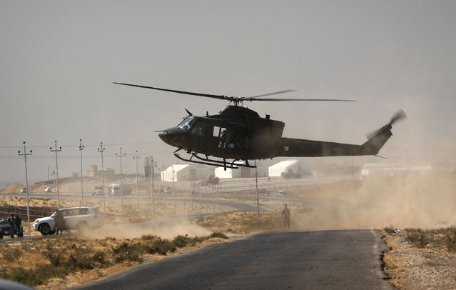 A helicopter lands on a road in Nawran village, some 10 km north east of Mosul, on October 20, 2016, during the ongoing operation to retake the city from the Islamic State (IS) group The operation is Iraq' s biggest in years and aims to wrest back Mosul, the country' s second city and the last major IS stronghold in Iraq. (Photo by Safin Hamed/AFP Photo)