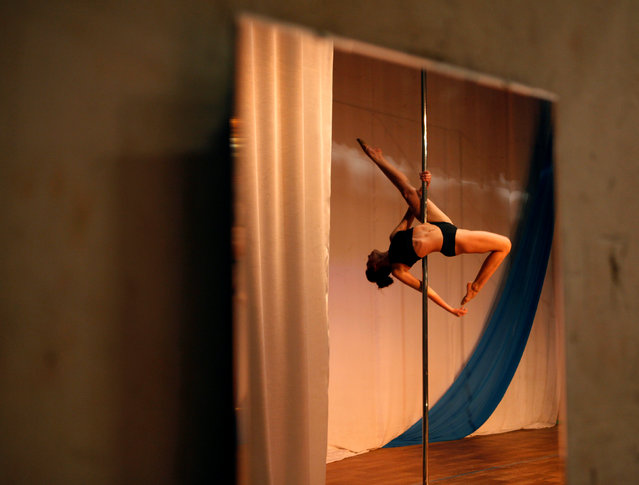 A participant is reflected in a mirror as she competes in the Perfect Pole 2016 pole dance championship in the southern city of Stavropol, Russia, October 22, 2016. (Photo by Eduard Korniyenko/Reuters)