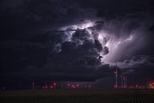 Lightning strikes in a black thunderstorm over wind turbines, on September 22, 2014, in Kansas. (Photo by Roger Hill/Barcroft Media)
