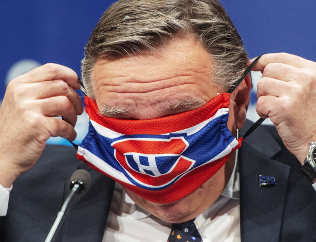 Quebec Premier Francois Legault puts on a Montreal Canadiens face mask as he finishes the daily COVID-19 press briefing, Thursday, May 21, 2020 in Montreal. (Photo by Ryan Remiorz/The Canadian Press via AP Photo)