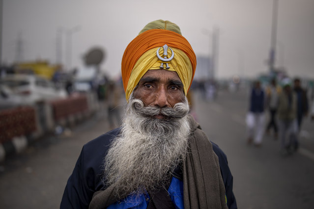 A Sikh farmer listens to a speaker from a distance as they block a major highway in a protest against new farm laws while it rains at the Delhi-Uttar Pradesh state border, India, Monday, January 4, 2021. Ignoring the coronavirus pandemic, the farmers have been blockading highways connecting New Delhi to northern India for nearly five weeks, obstructing transportation and dealing a blow to manufacturing and businesses in the north. (Photo by Altaf Qadri/AP Photo)