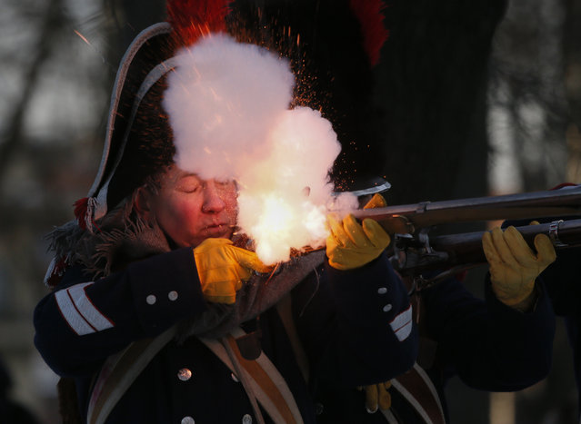 A member of an historic club wearing 1812-era French army uniform fires his rifle,  during an historic festival to mark the Russian Orthodox Christmas in St. Petersburg, Russia, Wednesday, January 7, 2015. (Photo by Dmitry Lovetsky/AP Photo)