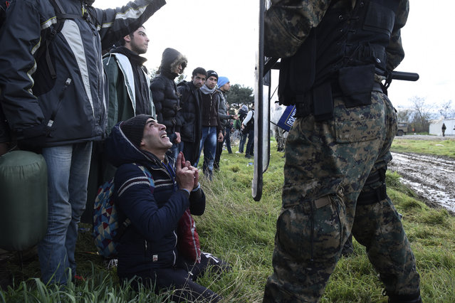A man kneels before a Macedonian police officer in an effort to cross the border, near the northern Greek village of Idomeni, Thursday, November 26, 2015. Scores of migrants stranded at Greece's northern border have clashed with police while trying to force their way into Macedonia. Macedonia toughened rules for migrant crossings earlier this month, restricting access to citizens from countries typically granted asylum in Europe, including Syria and Afghanistan. (Photo by Giannis Papanikos/AP Photo)