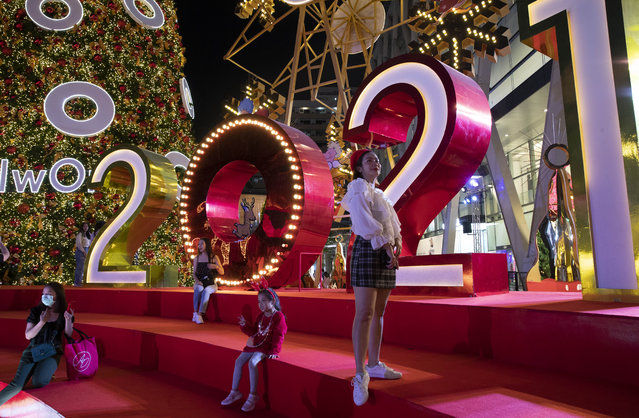 People pose for pictures with decorations made for New Year countdown celebrations outside a shopping mall in Bangkok, Thailand, Tuesday, December 29, 2020. Thailand ordered to scaled down gathering for New Year celebrations after reporting more than 155 new coronavirus infections and its first fatality since November on Tuesday. (Photo by Gemunu Amarasinghe/AP Photo)