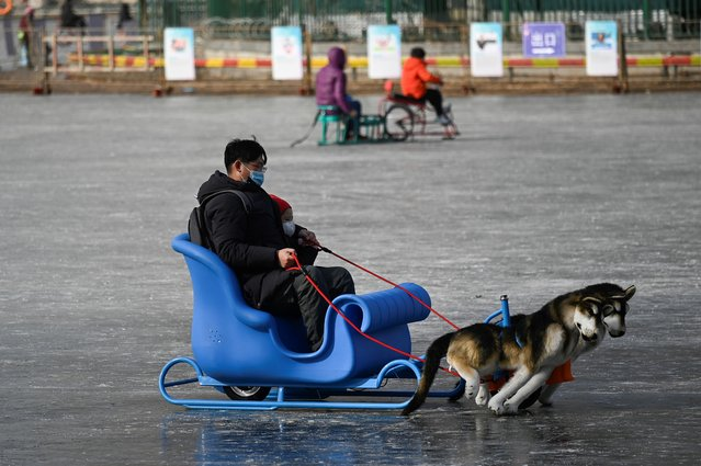 A man and a child use a sled on a frozen lake in Beijing on January 12, 2021. (Photo by Wang Zhao/AFP Photo)