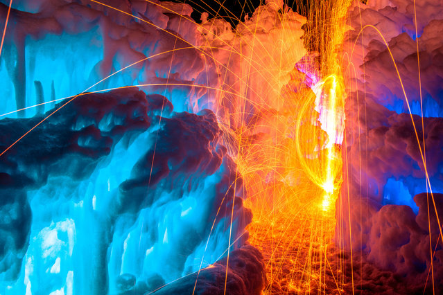 A photographer has discovered a spectacular way of keeping warm during winter – using fire to heat up icy locations. Sam Scholes uses long-exposures to capture the movement of fire in front of ice-covered backdrops. After lighting steel wool his friend Scott Stringham swings the flaming object in order to make swirling patterns. (Photo by Sam Scholes/Caters News)