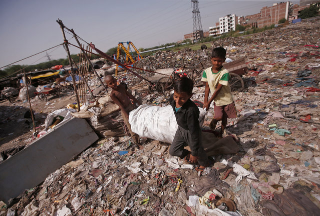 Boys carry a sack filled with recyclable material collected by them at a slum area in New Delhi, India, April 23, 2018. (Photo by Adnan Abidi/Reuters)