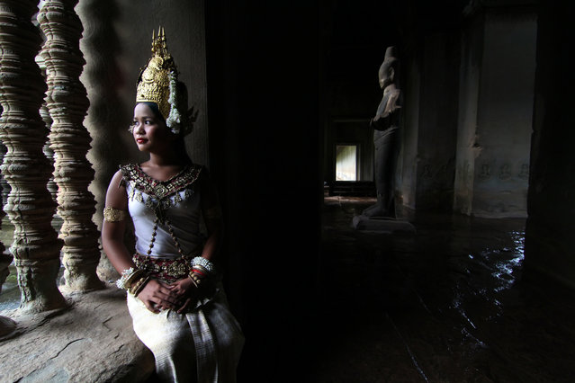 """""""Apsara dancer in deep thought"""". This Apsara dancer was in deep thought. She was seated inside the Angkor Wat temple in Siem Reap with a statue in shadow and water dripping past on the ground. Location: Siem Reap, Cambodia. (Photo and caption by Bonnie Stewart/National Geographic Traveler Photo Contest)"""