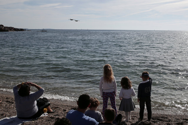 Spectators watch a pair of CL-215 firefighting aircrafts, during a show marking the Hellenic Air Force's Patron Saint celebration, on the southern suburb of Faliro, in Athens, Greece, November 6, 2016. (Photo by Alkis Konstantinidis/Reuters)