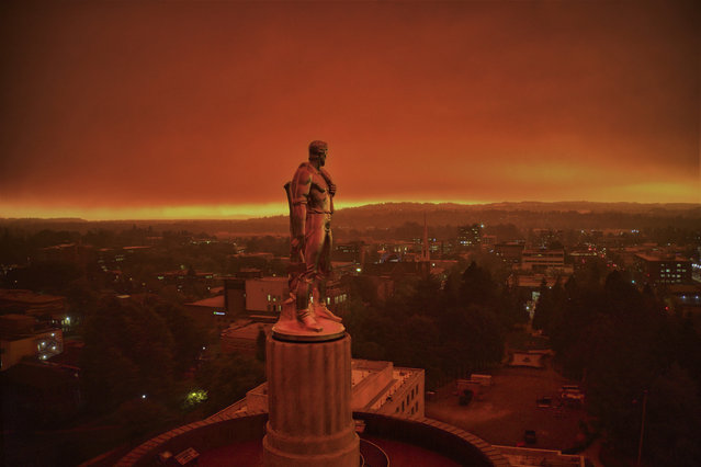 The Oregon Capitol building, and the Pioneer sculpture, are foregrounded against skies filled with smoke and ash from wildfire in Salem, US on September 16, 2020. (Photo by Michael Mann/AP Photo)