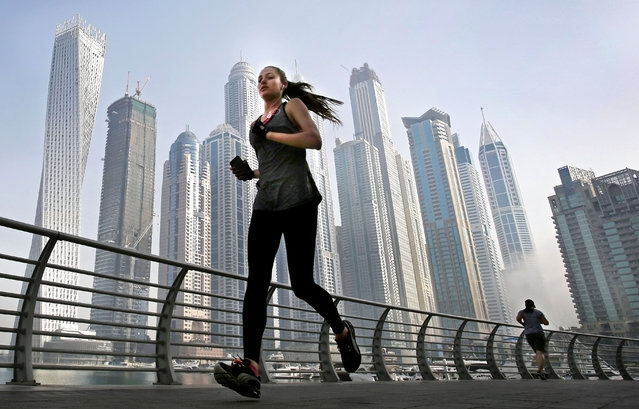 In this April 9, 2015 photo, as the early morning fog lifts, a woman jogs in front of giant skyscrapers at the Marina waterfront in Dubai, United Arab Emirates. (Photo by Kamran Jebreili/AP Photo)