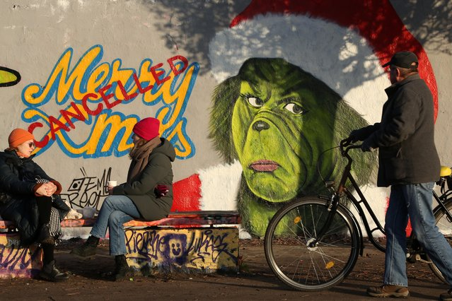 Graffiti proclaiming the cancellation of Christmas, featuring the Dr. Seuss Grinch character, is seen on a section of the former Berlin Wall amidst a nationwide hard lockdown before the holiday during the second wave of the coronavirus pandemic on December 21, 2020 in Berlin, Germany. Authorities have resorted to the lockdown in an attempt to bring down daily infection and death rates that have reached record highs despite a semi-lockdown that had been in place since November. The new lockdown will last at least until January 10. (Photo by Adam Berry/Getty Images)