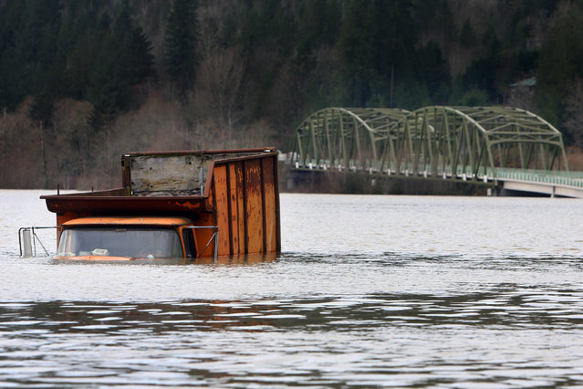 A truck is submerged floodwaters from the Snoqualmie River off of Tolt Hill Road in Carnation, Wash., Wednesday, December 9, 2015. Torrential rains pummeled parts of the Pacific Northwest early Wednesday, causing mudslides and flooding roads. (Photo by Genna Martin/seattlepi.com via AP Photo)