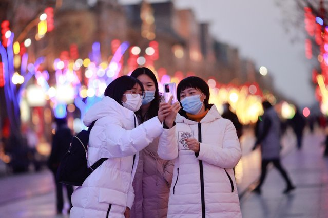 People take a selfie in a historic street decorated for Lunar New Year celebrations, following an outbreak of the coronavirus disease (COVID-19), in Beijing, China, February 8, 2021. (Photo by Thomas Peter/Reuters)