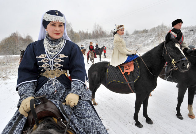 Riders in period costume take part in a re-enactment of a 19th-century hunting expedition with hounds, near the village of Pionino, in the Dzerzhinsk district of central Belarus on November 11, 2016. Hunting is still a national pastime in Belarus, where moose and red deer, capercaillie, black grouse and woodcock are among the many species roaming its extensive wildernesses. Medieval festivals and re-enactments of battles, hunts and sailing expeditions are an increasingly popular feature of the country's cultural calendar. (Photo by TASS/Barcroft Images)
