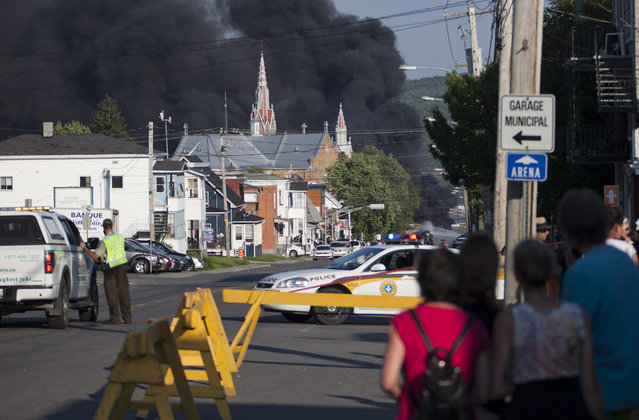 Residents watch rising smoke after a freight train loaded with oil derailed in Lac Megantic, on July 6, 2013. (Photo by François Laplante-Delagrave/AFP Photo)