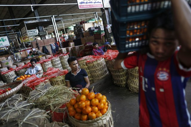 Workers unload oranges at Thiriminglar fruit, vegetable and flower wholesale market in Yangon January 23, 2015. (Photo by Soe Zeya Tun/Reuters)