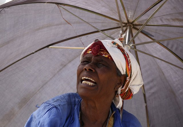 A stall owner shields herself from the sun with an umbrella as she talks to a customer at the Mercato market in Addis Ababa November 28, 2015. (Photo by Tiksa Negeri/Reuters)