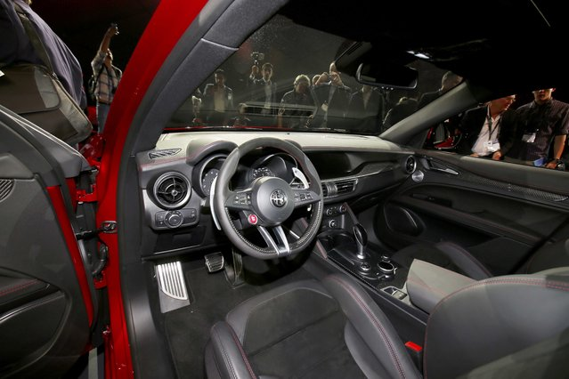 People look over the interior of the car as Alfa Romeo introduces the 2018 Stelvio SUV at the 2016 Los Angeles Auto Show in Los Angeles, California, U.S November 16, 2016. (Photo by Mike Blake/Reuters)