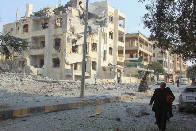 A man walks past damaged buildings after what activists said were airstrikes carried out by the Russian air force in Idlib city, Syria December 20, 2015. (Photo by Ammar Abdullah/Reuters)