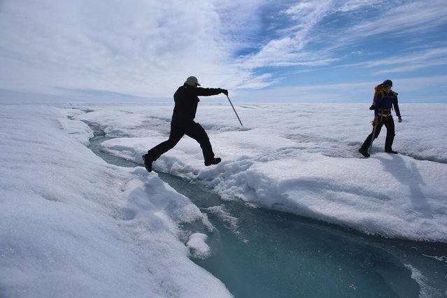 Scientist Ian Joughin of the University of Washington leaps over a small meltwater stream as he walks with Graduate Student, Laura Stevens, from the Massachusetts Institute of Technology and Woods Hole Oceanographic Institution as they conduct research on July 16, 2013 on the Glacial Ice Sheet, Greenland. (Photo by Joe Raedle/Getty Images via The Atlantic)